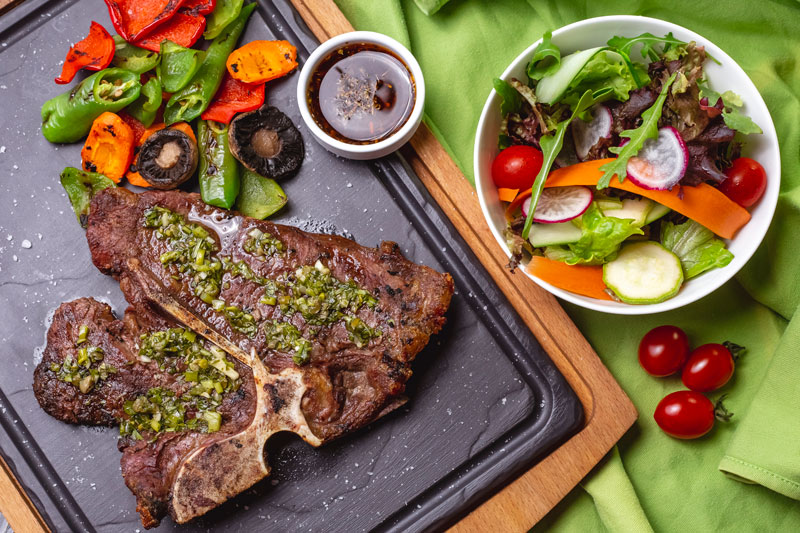 Diễn đàn rao vặt tổng hợp:  T-bone-steak-with-greens-bell-pepper-tomato-carrot-mushroom-with-green-salad-bowl-top-view